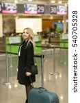 Small photo of Off I go. Vertical shot of a beautiful young business woman smiling over her shoulder to the camera while heading to check-in desk at the airport terminal