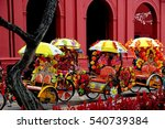 Small photo of Melacca, Malaysia - December 27, 2006: A row of colourful tri-shaw taxis decorated with plastic flowers parked in front of 1753 Christ Church await fares