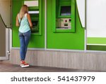 Young Woman Using A Cash Point...