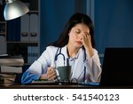 Small photo of Closeup portrait sad unhappy health care professional with headache stressed sleepy holding cup of coffee. Nurse doctor with migraine overworked overstressed. pretty mixed race asian chinese woman