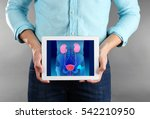 Small photo of Man with tablet in hands. Urinary system on screen. Urology concept.