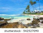 Ocean coast with stones in the palm island Sri Lanka. Resort Unawatuna.