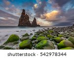 Sunset cloudscape over rocky coast with monumental rocky cliff and blurred sea water. Madeira island, Portugal - stock photo