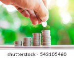 Small photo of Businessman showing collect many coins with fresh nature blurred background and sunlight.