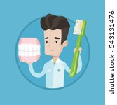 young friendly dentist holding...   Shutterstock .eps vector #543131476