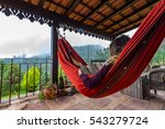 Tourist relaxing on terrace in wooden hammock, reading the book. - stock photo
