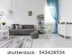 Small photo of Bright spacious living room with comfortable couch and chest of drawers