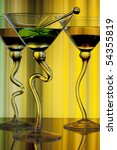 Three wine glasses with curved stems full of liqueur on yellow background - stock photo