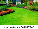 Front yard, landscape design With multicolored shrubs intersecting with bright green lawns Behind the house is a modern, garden care service, green grass with a beautiful yard for the background. - stock photo