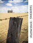 Rusty barbed wire fence with harvested wheat field and grain silo's in background - stock photo
