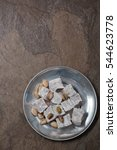 Small photo of Turkish delight candies with pistachios on a pewter plate. Dark brown stone background. Copy space.