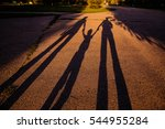 Small photo of the shadow of a family on earth