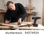 Young carpenter working in his workshop with tools - stock photo