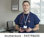 doctor holding and reading tablet in his office in between patients - stock photo