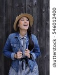 Small photo of Laughing smile asian woman with an wearing hat and good sense of humor smiling as she tilts her head back to look into the air