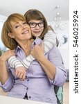 Small photo of Portrait of affectionate daughter embracing mother at home