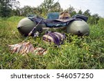 Small photo of Good catch. Float tube with rod and fish entrapment against the background of water grass.