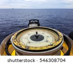 Small photo of Compass aboard large ship on a blue summer sea ocean day