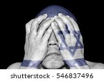 Small photo of A man covering his eye with his hand with imprint of the Israeli flag for the concept: Justice is blind in Israel.