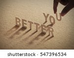 Small photo of BETTER YOU wood word on compressed or cork board with human's finger at U letter.