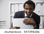 Small photo of Portrait of a very shy African American office clerk working in a white office, smiling and grasping his laptop as a treasure. Concept of shyness and social awkwardness