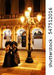 Blurry image of two mysterious female masks at San Marco square at night during the Carnival. Venice (Italy) - stock photo