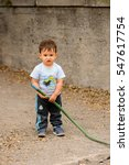 Small photo of SANTIAGO, CHILE - NOV 1, 2014: Unidentified Chilean little boy plays with a hose. Chilean people are mainly of mixed Spanish and Amerindian descent
