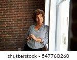 mature businesswoman standing... | Shutterstock . vector #547760260