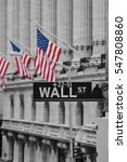 Small photo of A wall street sign in front of the American flags