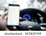 Picture blurred  for background abstract and can be illustration to article of Hand using a smartphone while driving a car - stock photo