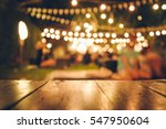 Stock photo image of wooden table in front of abstract blurred restaurant lights background 547950604