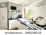 Stock photo functional modern white kitchen with cabinets stove and window 548148529