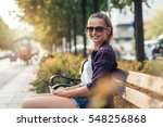 Young Woman Sitting On City...