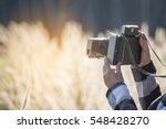 A beautiful woman holding a old polaroid camera. Standing in the meadow with sunset background.