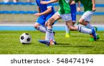 young boys kicking football on... | Shutterstock . vector #548474194
