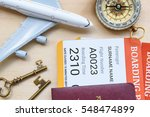 Small photo of Top view of two boarding pass with passports on a wood floor, decorated with a compass, a white model airplane, brass keys. Concepts about aviation, travel or transportation by air, vacation trip, etc
