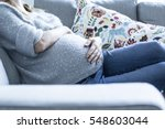 pregnant woman resting on a sofa | Shutterstock . vector #548603044