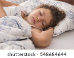 little girl sleeps in a bed on... | Shutterstock . vector #548684644