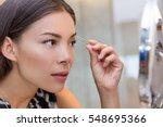 Asian Woman Plucking Eyebrows...