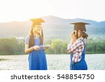Two Young Girls Graduate Being...
