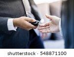 car salesman handing over the... | Shutterstock . vector #548871100