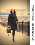 Small photo of beautiful smiling businesswoman quick step moves along the promenade along the river in a big city. fashion. instagram image filter retro style