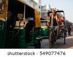 Small photo of DELHI, INDIA - 9 MARCH 2013: A Rickshaw driver rides behind a auto-rickshaw in Paharganj, Delhi. Delhi is the 2nd most populous city in India behind Mumbai.