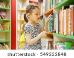 Small photo of preschooler choosing books at library.