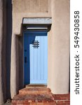 Small photo of a colorful door on an adobe structure