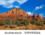Arizona, Sedona, Cathedral Rock mountain range; in the Coconino National forest. Blue skies and billowing white clouds cover the enriched red oxide cliffs, and vast desert    landscape.