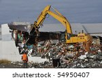 Loader Demolishing a Brick Building - stock photo