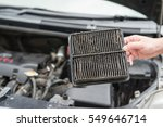 Small photo of Technician holding dirty air filter for car