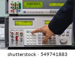 Small photo of a man adjust a parameter of calibrator meter to make a calibration of electronic meter