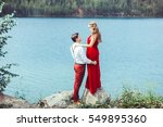 couple standing by a lake in an ... | Shutterstock . vector #549895360